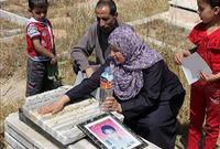 أسرة محمد الدرة خلال زيارتها لقبر ابنها الشهيد