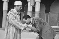 صورة للحسن يقبّل يد أبيه السلطان محمد الخامس وهي الطريقة الأكثر شيوعًا للتعبير عن الاحترام داخل الأسرة في المغرب.