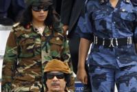 القذافي مرتديًا زيه الغير تقليدي واضعًا عليه كذلك خريطة قارة أفريقيا