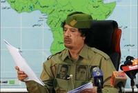 القذافي خلال إلقاءه خطابًا في التلفزيون مرتديًا قميص مطبوع عليه عبد الناصر وأحمد بن بلة