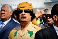 القذافي مرتديًا زيًا عسكريًا واضعًا عليه خريطة قارة أفريقيا