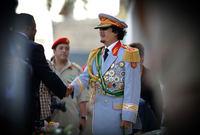 القذافي في بدلة عسكرية رسمية ذات لون غير تقليدي بها عدد كبير من النياشين والأوسمة العسكرية
