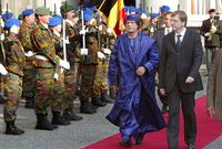 القذافي خلال استقبال رسمي له مرتديًا زيًا أزرقًا بالكامل غير تقليدي