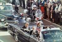 كان الموكب الرئاسي يمر عبر مدينة دالاس بسيارة مكشوفة وكان كيندي برفقة زوجته ويرافقهما حاكم ولاية تكساس جون كونالي